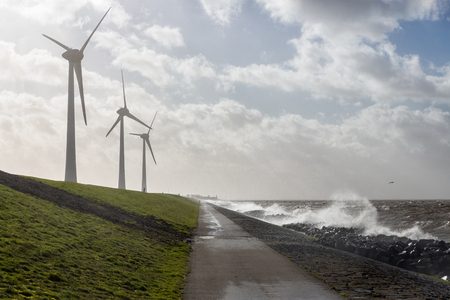 Dutch coast with windturbines and view at the skyline village urk. Stormy waves are breaking at the coast