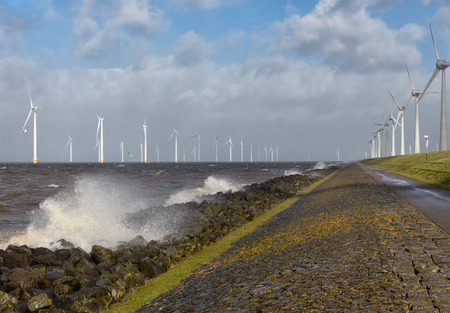 Dutch sea with off shore wind turbines and breaking waves at the shore Stockfoto