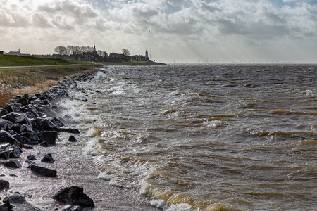 Dutch coast with backlight view at skyline village Urk. Stormy waves are breaking at the coast