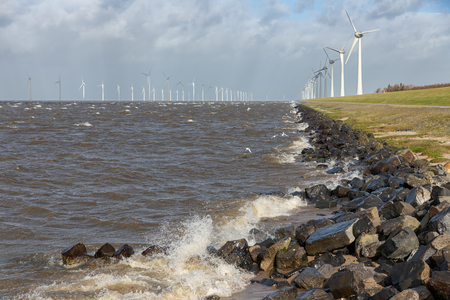 Dutch sea with off shore wind turbines and breaking waves at the shore Stockfoto - 118514260