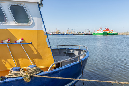 Stern fishing ship with mooring rope in Dutch harbor of Lauwersoog