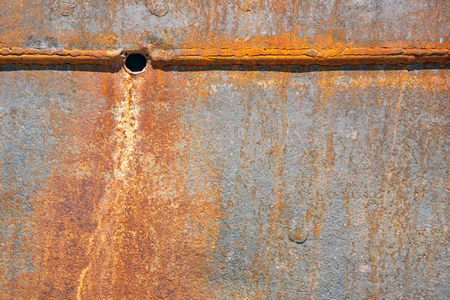 Background of rusty plating of ship with water hole at shipyard for maintenance