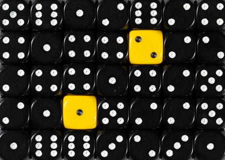 Pattern background of random ordered black dices with two yellow cubes