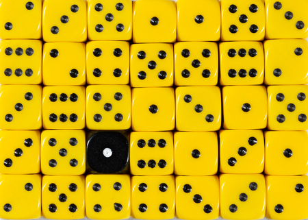 Pattern background of random ordered yellow dices with one black cube