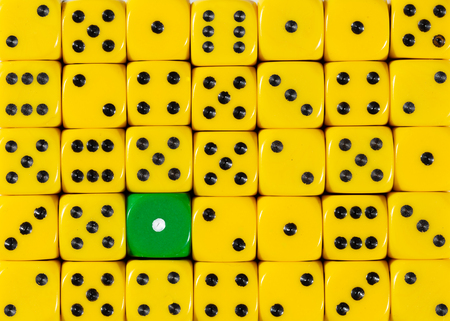 Pattern background of random ordered yellow dices with one green cube Stok Fotoğraf