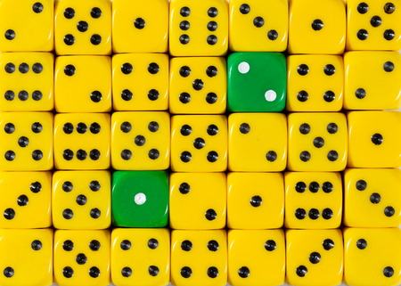 Pattern background of random ordered yellow dices with two green cubes