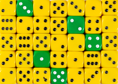Pattern background of random ordered yellow dices with five green cubes