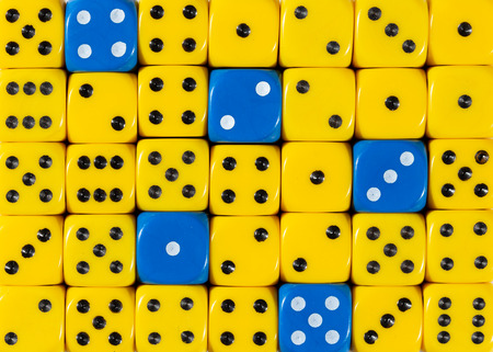 Pattern background of random ordered yellow dices with five blue cubes