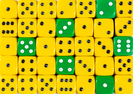 Pattern background of random ordered yellow dices with six green cubes