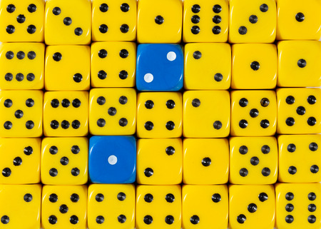 Pattern background of random ordered yellow dices with two blue cubes
