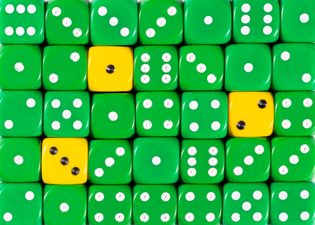 Pattern background of random ordered green dices with three yellow cubes