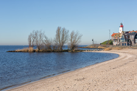 Beach of former Dutch island Urk with view at historic Lighthouse