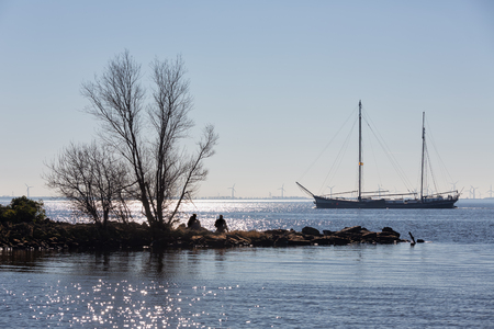 Spring backlight silhouet of breakwater in sparkling sea with two boys relaxing in the sun sitting at the stones near a bare tree, a historic sailing ship is passing
