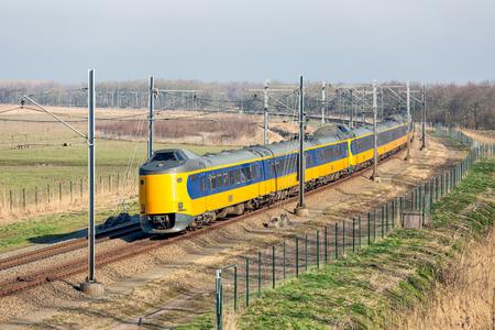 Dutch railway with express train through National Park Oostvaardersplassen between Lelystad and Almere