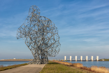Iron statue of a man sitting on his heels on an enclosure dam in Lelystad, The Netherlands