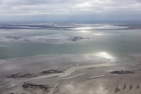 Aerial view at Dutch Wadden Sea with low tide, the sun is reflecting at the water