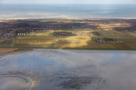 Aerial view Dutch island Schiermonnikoog while the sunlight is shining at the fields Stock Photo