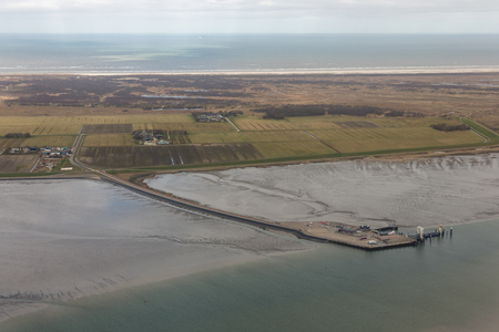 Aerial view Dutch island Schiermonnikoog with pier ferry terminal at low tide