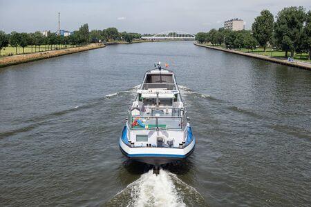 Large inland ship at Dutch Amsterdam Rijn canal sailing near city Utrecht