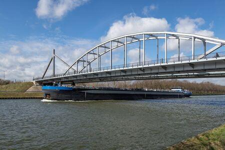 Grand bateau intérieur au canal hollandais d'Amsterdam Rijn passant un pont en acier Banque d'images