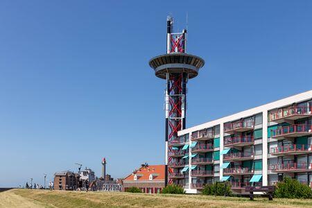 Seascape harbor Dutch city Vlissingen at Westerschelde with lighthouse , watch tower and houses Banco de Imagens