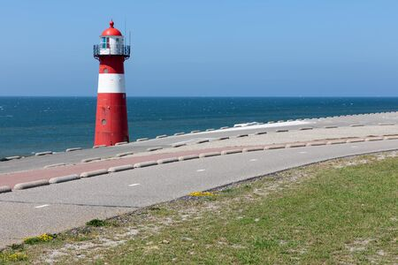 Lighthouse at dike near Westkapelle in the Netherlands Stockfoto