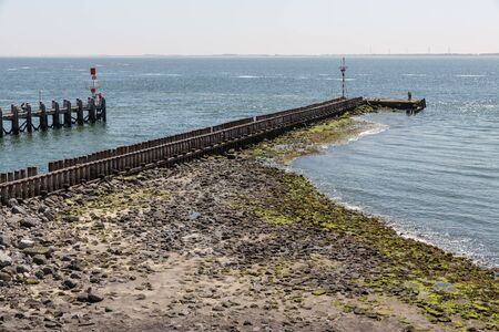 Entry Dutch harbor Vlissingen at Westerschelde with wooden jetty and fishing people