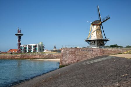 Traditional windmill at dike near WW2 battlefield Uncle Beach at Vlissingen, The Netherlands Banco de Imagens