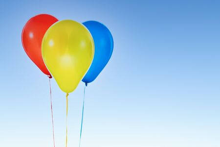 Three red, yellow an blue helium balloons for birthday and celebrations isolated at blue sky with copy space for free text