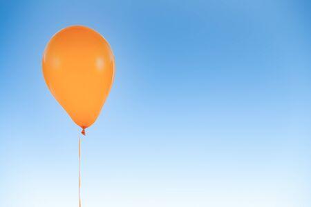 Globo de fiesta de helio naranja para cumpleaños y celebraciones aislado en el cielo azul con espacio de copia para texto libre Foto de archivo