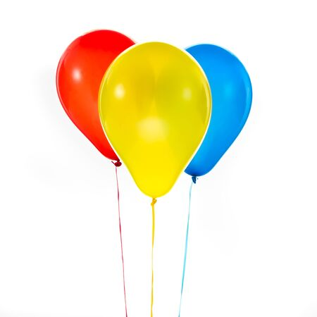 Three red, yellow an blue helium balloons for birthday and celebrations isolated on white background