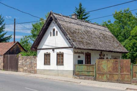 Szomolya , Hungary - July 07, 2019: Tiny house with white walls and reed roof in Szomolya, Hungary