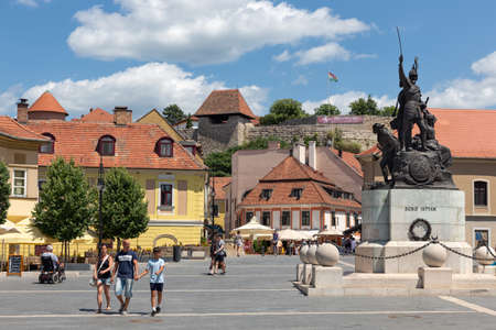 Eger , Hungary - July 08, 2019: Family walking at main square Eger with statue of Istvan Dobo