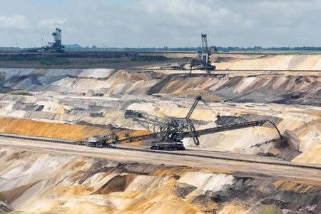 Digging machines busy with deposit of unused soil in Hambach open pit mine Germany