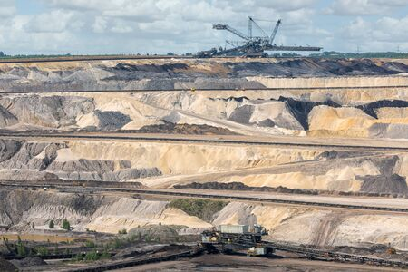 Brown coal open pit landscape with enormous digging machine moving mullock and soil in Garzweiler mine Germany