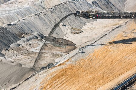 Digging machine busy with deposit of unused soil in Hambach open pit mine Germany
