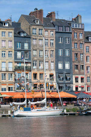 HONFLEUR, FRANCE - AUGUST 24, 2017: Cityscape medieval city Honfleur with manoeuvring sailing ship in harbor Redactioneel