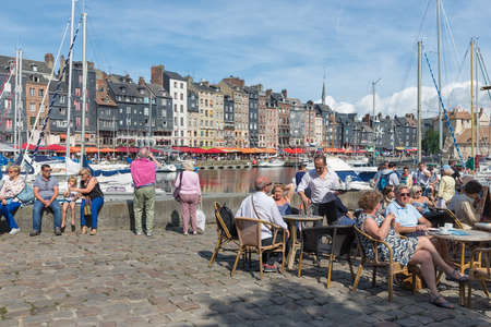 HONFLEUR, FRANCE - AUGUST 24, 2017: Harbor of historic city Honfleur with people sitting at terrace of restaurant