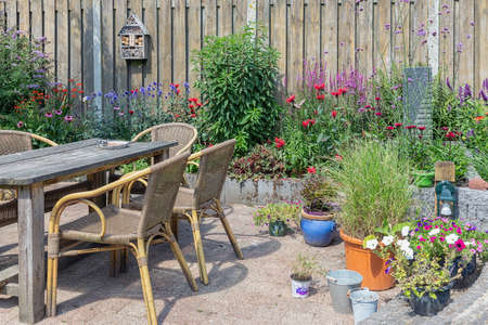 Ornamental garden with colorful plants in flowerbed and wooden table with chairs