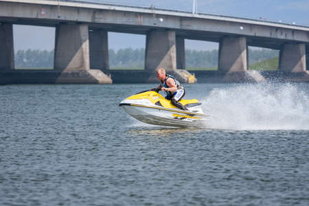 Lelystad, The Netherlands- May 01, 2009: Man having fun on Jet Ski near Dutch Ketel Bridge 新闻类图片