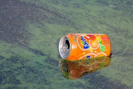 Urk, The Netherlands- July 31, 2009: Soda can of fanta floating in Dutch harbor Urk with many algae 新闻类图片