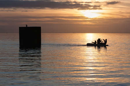 Urk, The Netherlands- December 28, 2009: Artist in rowing-boat pulls a floating house he has build for an artistic project, His action is filmed for the Dutch television. 新闻类图片