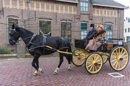 Urk, The Netherlands- February 13, 2010: Man and woman at horse-drawn carriage during festival in Dutch village Urk 新闻类图片