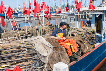 Urk, The Netherlands- May 21, 2011: Fishing ship with young fisherman repairing nets while sitting at a heap of fishing nets