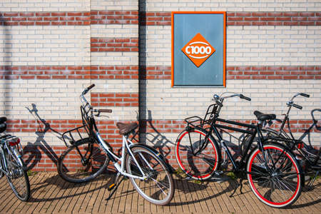 Urk, The Netherlands- July 04, 2011: Parked bicycles against wall with billboard of Dutch supermarket C1000