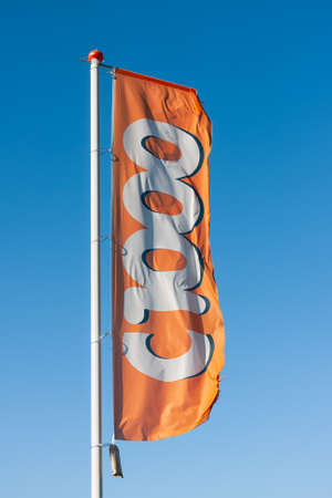 Urk, The Netherlands- July 04, 2011: Flag of Dutch drugstore C1000 blowing in the wind 新闻类图片