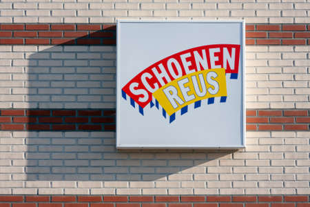 Urk, The Netherlands- July 04, 2011: Brick wall with billboard of Dutch shop chain Schoenenreus