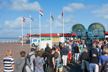 Hollum, The Netherlands- August 02, 2011: Passengers waiting near terminal for Ferry from Holwerd to Dutch island Ameland 新闻类图片