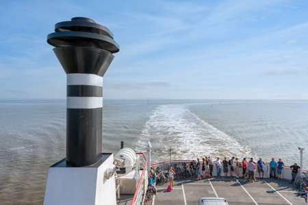 Hollum, The Netherlands- August 02, 2011: Passengers looking to wake at deck Ferry from Holwerd to Dutch island Ameland 新闻类图片