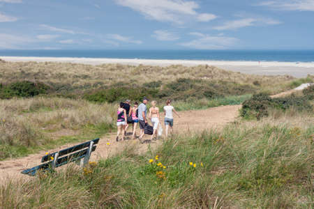 Ameland, The Netherlands- August 02, 2011: Seaside visitors walking over sandy path through dunes to beach of Dutch island Ameland